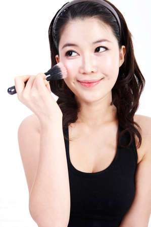 leisureliness: Young woman applying make up LANG_EVOIMAGES