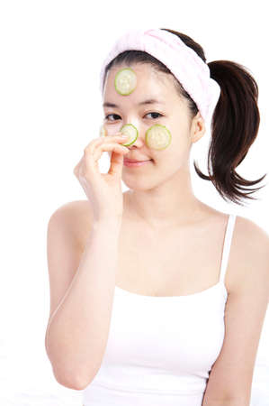 leisureliness: Young woman applying cucumber on face, portrait LANG_EVOIMAGES