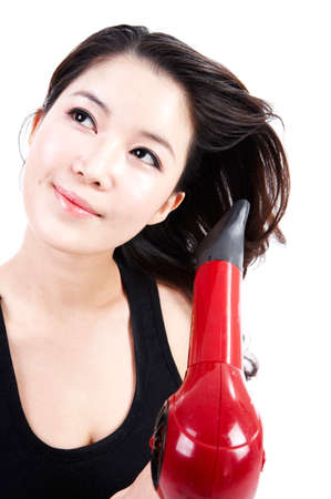 leisureliness: Young woman drying hair with hair dryer, close up LANG_EVOIMAGES