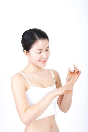 leisureliness: Young woman applying nail polish LANG_EVOIMAGES