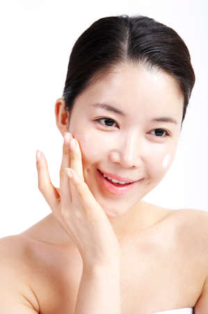 youthfulness: Young woman applying face cream