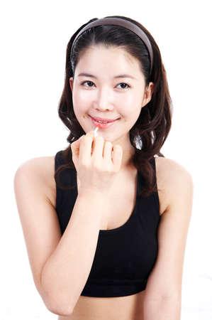 leisureliness: Young woman applying lip gloss