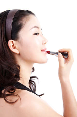 leisureliness: Young woman applying lipstick LANG_EVOIMAGES