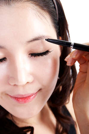 eye liner: Young woman applying eye liner, close up