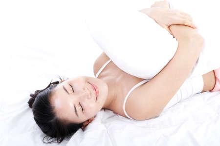 woman lying down: Young woman lying down hugging pillow