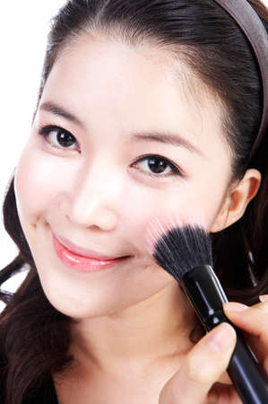 fair skin: Young woman applying make up, close up LANG_EVOIMAGES