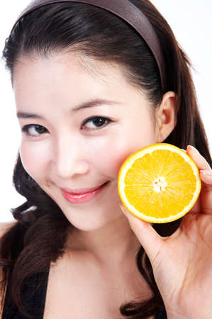 fair skin: Young woman holding sliced orange, close up LANG_EVOIMAGES