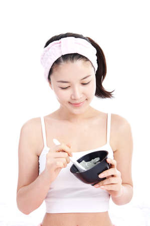 attractiveness: Young woman preparing face pack