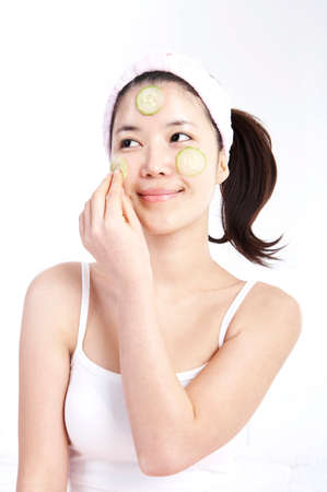 leisureliness: Young woman applying cucumber on face