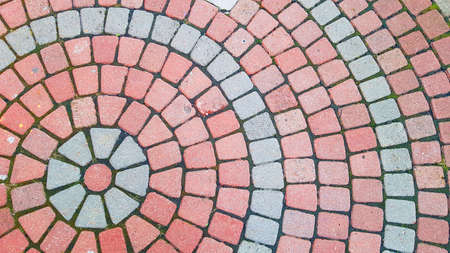 Round square area paved with red grey stones . Concentric lines of road tiles cover top view. Circle pavement pattern