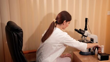 medicine, hospital, young beautiful woman doctor, nurse in white medical gown, sitting in the office and using microscope, health concept, slow motion