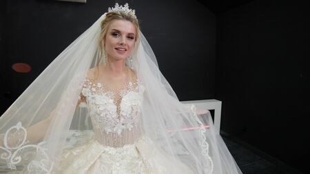 Young beautiful bride in white wedding dress sits on bed plays with veil throws it at camera in black room