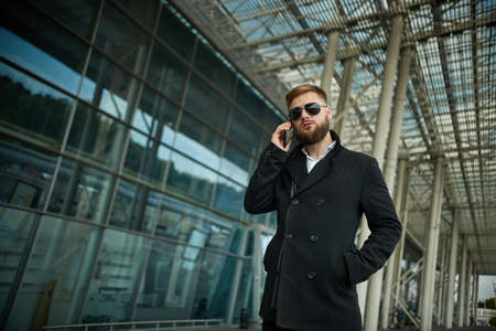 Urban business man in sunglasses talking smart phone traveling walking outside airport. Casual young businessman wearing suit jacket. Handsome male model in 20s, Manager, City Hall, cell.