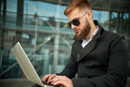 Manager holding laptop, Out of office work, young businessman in sunglasses using computer for his job at outside. Handsome bearded hipster, Communication and technology, in the open air, Surfing