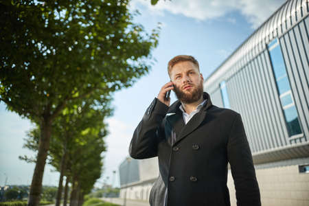 Urban business man talking smart phone traveling walking outside airport. Casual young businessman wearing suit jacket. Handsome male model in 20s, Manager, City Hall, cell Standard-Bild