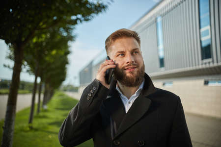 Urban business man talking smart phone traveling walking outside airport. Casual young businessman wearing suit jacket. Handsome male model in 20s, Manager, City Hall, cell. Close up Standard-Bild