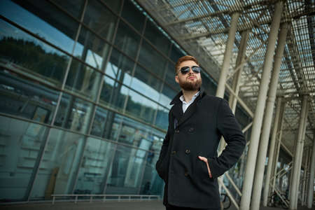 Success. Stylish young bearded man in coat, sunglasses businessman standing near the business center, looking far. With hands pockets, pensive and concentrated. Confident look of