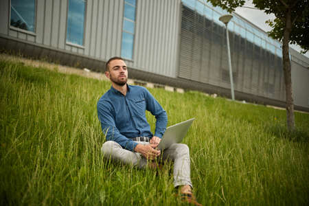 Manager holding laptop, Out of office work, young businessman using computer for his job at outside. Handsome bearded hipster, Communication and technology, in the open air, Surfing 스톡 콘텐츠