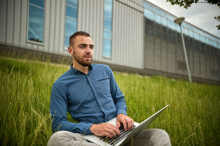 Manager holding laptop, Out of office work, young businessman using computer for his job at outside. Handsome bearded hipster, Communication and technology, in the open air, Surfing Standard-Bild