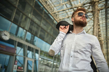 Handsome young man walking in an urban street with jacket slung over shoulder as he looks away, close up upper body view. Attractive male hipster model. Low angle of businessman cloak suit outdoors 스톡 콘텐츠