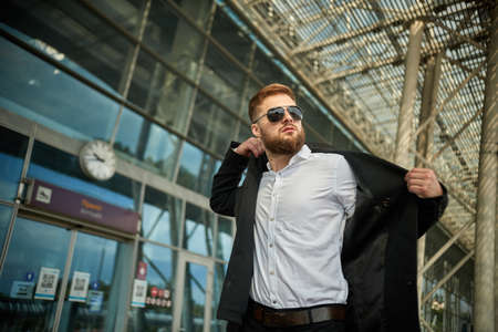 Close up of businessman putting on raincoat in city, man puts coat outside, boss or worker black suit. Serious pensive person standing sunglasses. Handsome young male office jacket. Glasses wearing