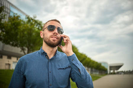 Handsome young male in glasses walking on the street, talking mobile phone. Communication. Man, outdoor. Person is speaking a telephone. Call with his smartphone.