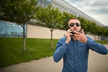 Man arguing over smart phone. Ouch someone is mad at me. Portrait of intense displeased young handsome male scolded by interlocutor via telephone holding smartphone. Furious businessman talking. Standard-Bild