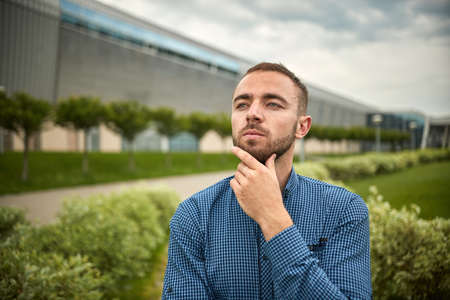Person thinking outside. Tired businessman looking. Focused business man thought. Guy has another hand on chin. He thinks. Young male stands in a blue shirt. Stock fotó