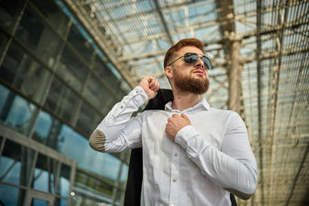 Handsome young man walking in an urban street with jacket slung over shoulder as he looks away, close up upper body view. Attractive male hipster model. Low angle of businessman cloak suit outdoors Standard-Bild