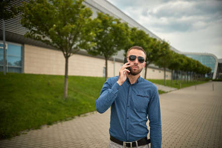 Traveler teen guy calling on the mobile phone. Portrait of confident young businessman dressed in formal clothes standing outside glass building, cell Standard-Bild