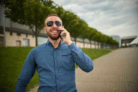 A young successful man, male executive businessman talking on his cell telephone celebrating. Excited person talks the mobile phone. Urban business human Standard-Bild