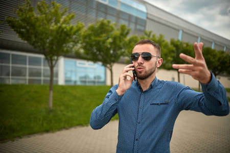 Aggressive young businessman screaming at smartphone while having mobile conversation. Angry male talk on smart phone arguing, solving problem, irritated person, customer service disputing
