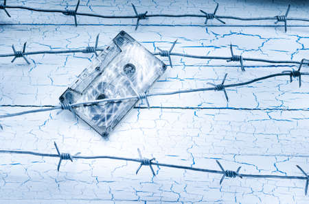 Audio cassette tape hanging on the barbed wire on the background of the old wall
