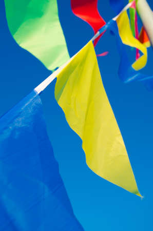 whiff: Dangling in the wind festive flags on the background of blue sky Stock Photo