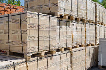 warehouse building: Large number of pallets of yellow brick Stock Photo