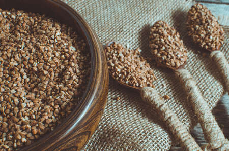 Buckwheat in a wooden bowl and a spoon full of buckwheat on the old burlap
