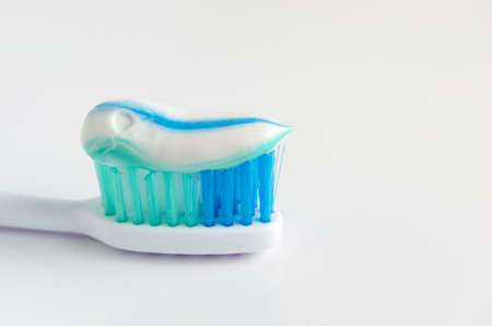 Toothpaste squeezed on the toothbrush on white background Stock Photo
