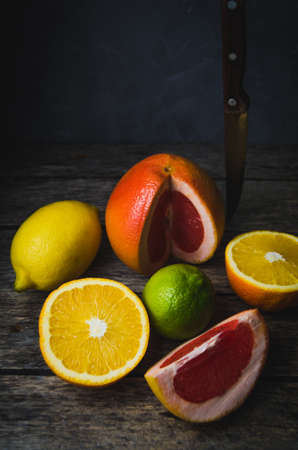 Tinted vertical photo of citrus fruits orange grapefruit lemon and lime on the old wooden table with knife