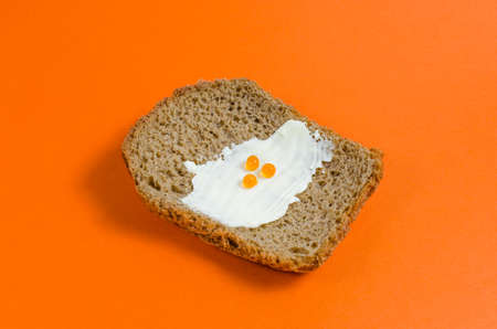 A piece of black rye bread, smeared with butter and red caviar on orange background