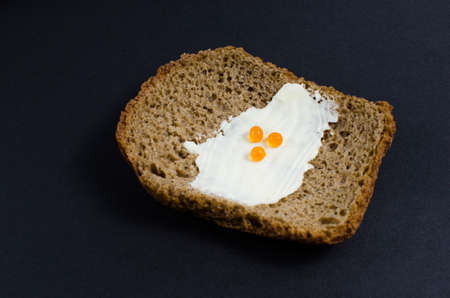 A slice of bread anointed with oil and red caviar on black background Stock Photo