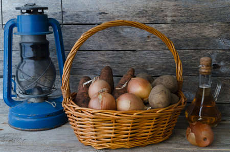 Potato tubers in a basket, carrot and onion with sunflower oil and the old oil lamp on a wooden background