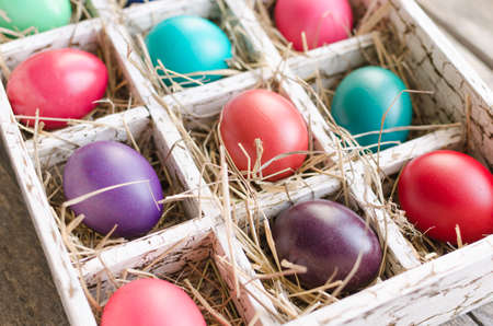 Easter eggs in a wooden box with hay lit by daylight