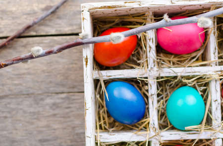 Willow twigs and Easter eggs in a wooden box on an old wooden table