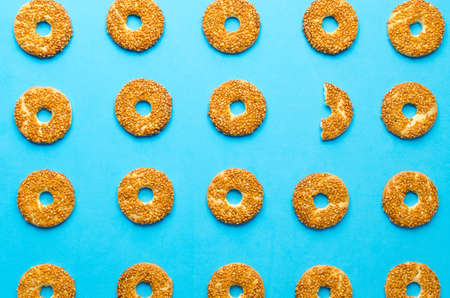 Round cookies with sesame seeds on a blue background, one cookie is not such as all. White crow. Stock Photo