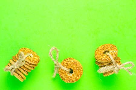 Round cookies with sesame seeds bound with a rope on a green background.