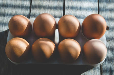 Chicken eggs on a wooden old table in the early sun. The shadows from the blinds fall on the background and eggs.