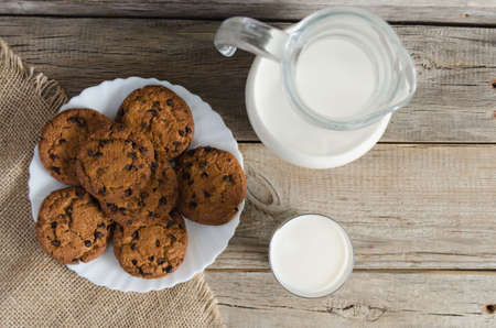 Biscuits, a jug and a glass of milk on burlap on old wooden table.The view from the top.