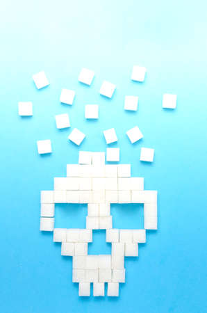 Refined sugar on blue background.Sugar cubes in form of skull.Concept of healthy eating, addiction to candy.Closeup.