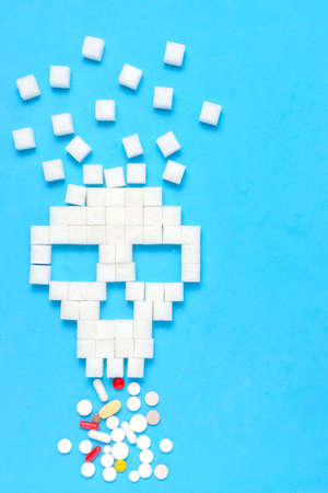Refined sugar in form of skull with tablets and pills.The concept of healthy eating.