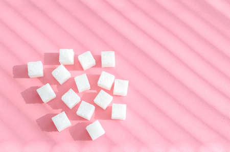 Refined sugar on pink background.Cubes of sweet and white sugar in geometricshape. Hard shadows and blinds.